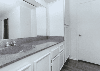 Marbled counter with wide mirror and sink leading to the closed door
