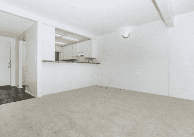 Living area showing the kitchen cabinets and wall light