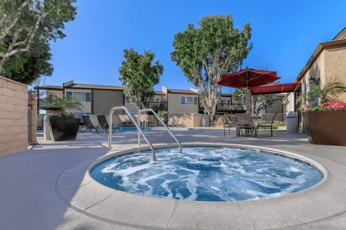 Jacuzzi Spa Pool surrounded by trees, red outdoor pool umbrella and chairs