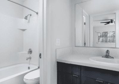 Bathroom showing the bathtub, toilet, bath sink counter and wide mirror